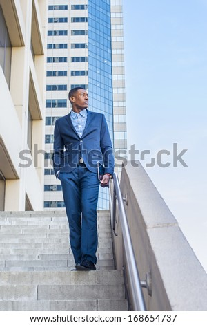 Holding a tablet computer, a young handsome black businessman is standing outside of a business building, confidently looking forward. - stock photo