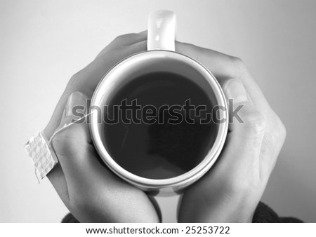 Holding a Tea Cup containing Green Tea - stock photo