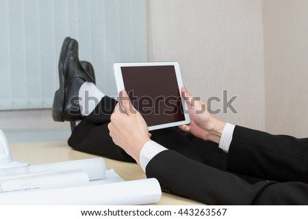 holding a white tablet with blank screen where you can place your text on a dark wooden table - stock photo