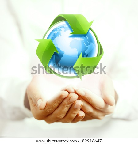 Holding blue earth and recycling arrows - stock photo
