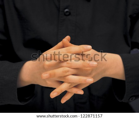 Holding both hands together with fingers crossed - stock photo