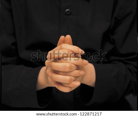 Holding both hands together with fingers crossed as praying - stock photo