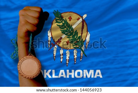 Holding bronze medal for sport and flag of us state of oklahoma - stock photo