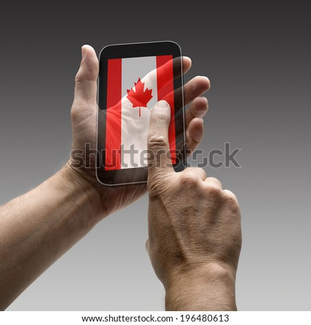 Holding canada flag screen smart phone. There is a route for hand and finger.  - stock photo