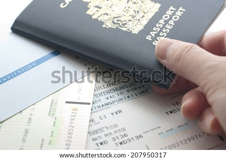 Holding Canada passport with boarding pass - stock photo