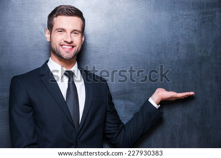 Holding copy space. Handsome young man in formalwear looking at camera and holding copy space while standing against blackboard - stock photo