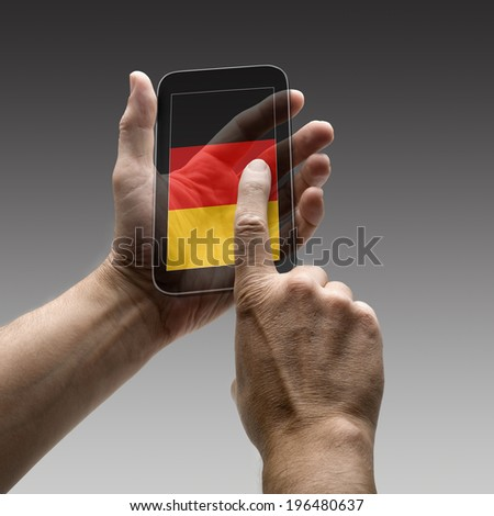 Holding germany flag screen smart phone. There is a route for hand and finger.  - stock photo