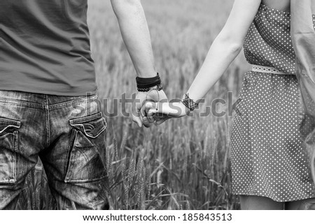 Holding hands couple black and white - stock photo