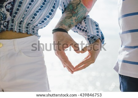 Holding hands, couple holding hands, bride and groom holding hands in the shape of heart - stock photo