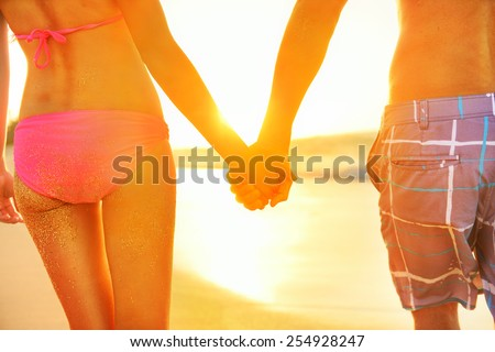 Holding hands couple in swimwear at beach. Rear view of fit couple's buttocks and legs as weight loss concept at beach sunset during summer vacations. - stock photo