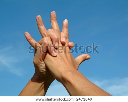Holding hands in love against blue sky - stock photo