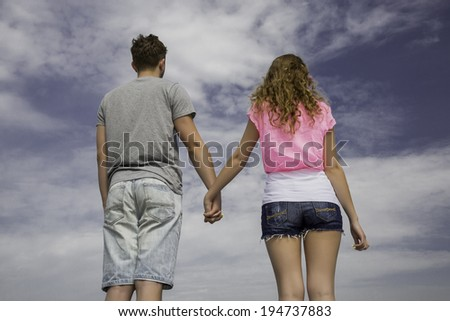 Holding hands. Male and female teens are holding hands of each other with the sky on background. - stock photo