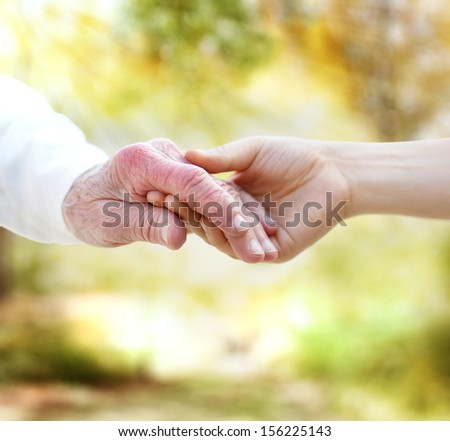 Holding hands with senior on autumn yellow foliage background - stock photo