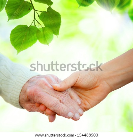 Holding hands with senior over green leaves background - stock photo