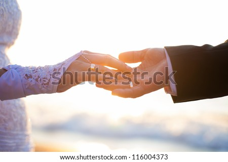 Holding Hands with wedding rings on the background of sea and sun. - stock photo