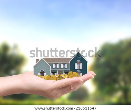 holding house representing home ownership and the Real Estate business holding house and coins  - stock photo