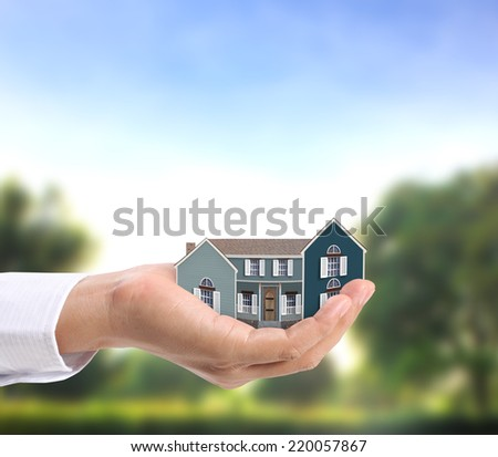 holding house representing home ownership ,the Real Estate business  - stock photo
