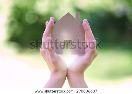 holding house sign in hands, light rays in the background - stock photo