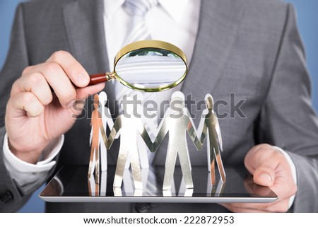 Holding magnifying glass and paper people. Closeup shot - stock photo