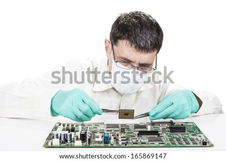 Holding Microchip on electronic circuit board with tweezers on white background - stock photo