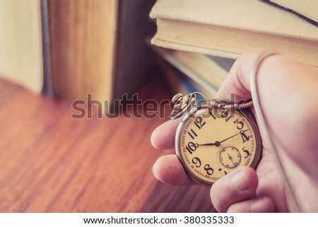 Holding old pocket watch in hand with stack of books behind - stock photo