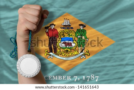 Holding silver medal for sport and flag of us state of delaware - stock photo
