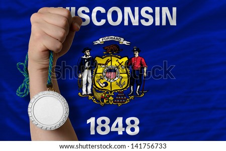 Holding silver medal for sport and flag of us state of wisconsin - stock photo