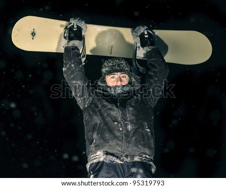 Holding snowboard high - stock photo