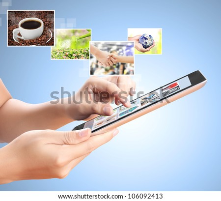 holding touch screen tablet with streaming images - stock photo