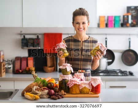 Holding up two jars of preserved vegetables, this happy, elegant woman is proud of all she has accomplished in preserving fresh vegetables. How tasty the winter months will be... - stock photo