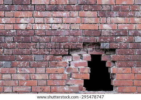 Hole in an old brick wall pattern showing damage to building - stock photo