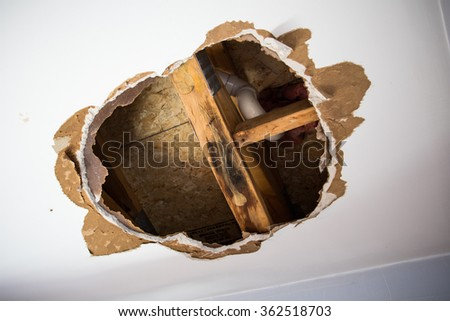 Hole in ceiling showing water and mold damage. - stock photo
