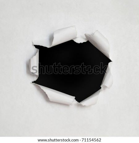 Hole in the paper with torn sides. - stock photo