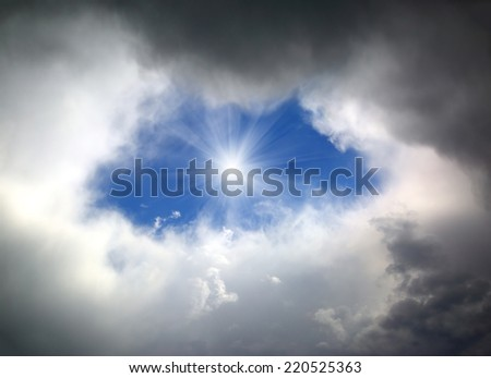 hole of blue sky in the dark clouds  - stock photo