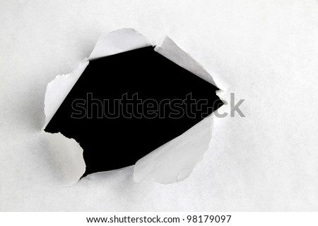 Hole ripped in paper on black background - stock photo