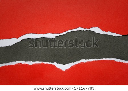 Hole ripped in red paper on black background - stock photo