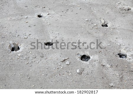 Holes in concrete after demolishing with jackhammer tool at construction site - stock photo