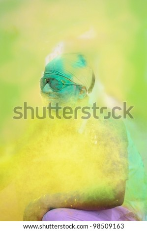 Holi celebrations - Closeup of an Indian boy playing holi in India. - stock photo