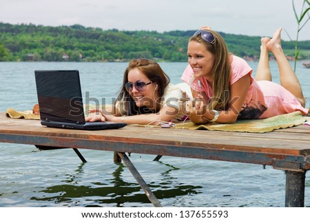Holiday and Internet / Two cheerful young woman use a laptop on holidays - stock photo