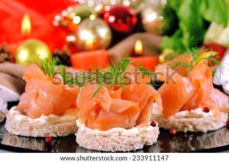 Holiday appetizer with salmon canapes on a background of Christmas decorations - stock photo