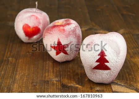 Holiday apples with frosted drawings on wooden background - stock photo