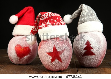 Holiday apples with frosted drawings on wooden table on black background - stock photo