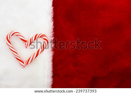 Holiday Background, A plush red stocking with a Candy Canes Heart with copy-space - stock photo