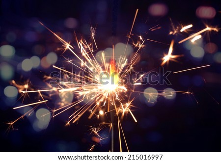 holiday background with a sparkler - stock photo