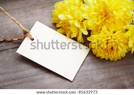 Holiday background with empty greeting card for text, and yellow asters on wooden table. - stock photo
