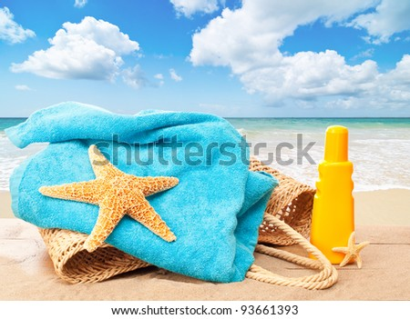 Holiday beach basket with towel and sun tan lotion overlooking an idyllic sandy beach - stock photo