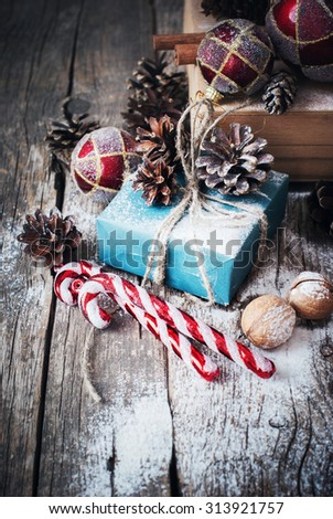 Holiday Blue Box with Gifts and Natural Twine, Balls, Pine Cones, Walnuts, Fir Tree Toys on Wooden Background. Toned image. Vintage style - stock photo
