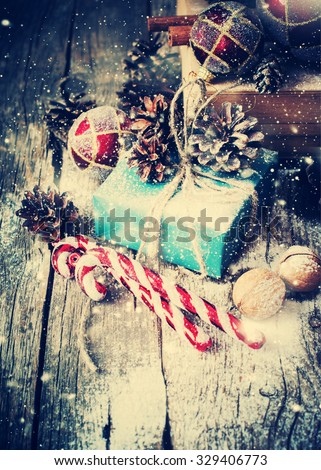 Holiday Blue Box with Gifts and Natural Twine, Balls, Pine Cones, Walnuts, Fir Tree Toys on Wooden Background. Toned. Vintage Style with Drawn Snowfall - stock photo