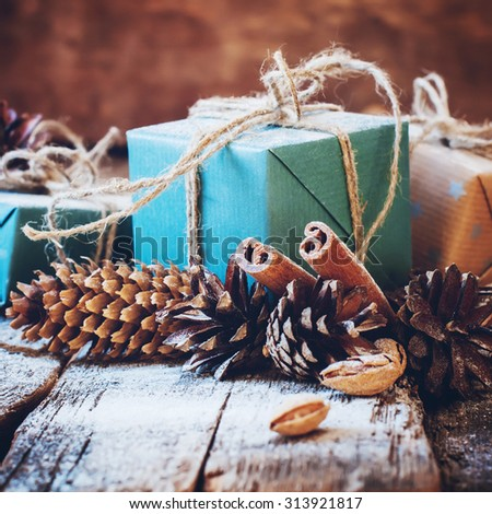 Holiday Boxes with Linen Cord, Cinnamon, Pine cones. Toned image - stock photo