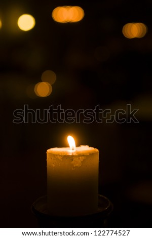 Holiday candle with blurred lights in background - stock photo
